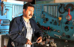 Kfz-Mechaniker bei einer 2-Saeulen-Hebebuehne